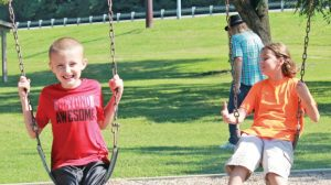Star Photo/Curtis Carden Two youngsters enjoy some time on the swings Friday morning at Cat Island Park.